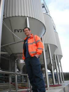 Stuart Howe, a giant of the brewing industry dwarfed by fermentation vessels at Sharp's Brewery, Cornwall